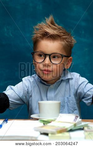 Portrait of stylish business child sitting at workplace with cash and crumpled papers, having break. Cute caucasian boy imitating businessperson or bookkeeper.