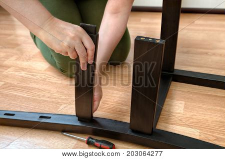 A woman assembles a dining chair from black wooden parts.