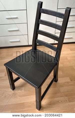 One dining chair made of black wood in the interior.