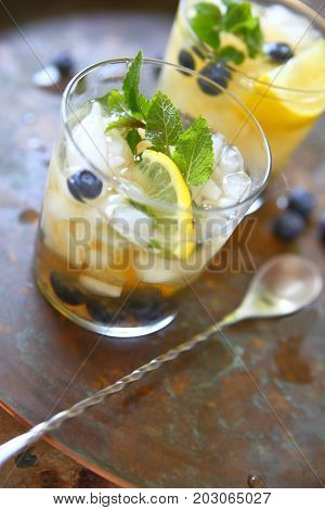 Two glasses of green tea with crushed ice lemon fresh blueberries and mint leaves