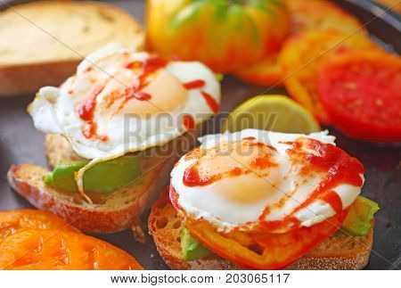 Sliced avocados on toast with fried eggs heirloom tomatoes and hot chili sauce
