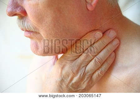 Older man with his hand against his throat natural light