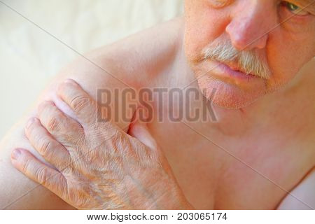 An older man with a hand on an aching shoulder joint