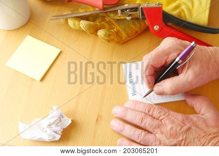 Overhead of man writing a to do list with crumpled paper notepad coffee cup gardening glove and grass cutters