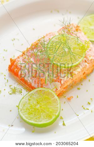 A serving of salmon roasted with garlic butter garnished with fresh lime slices and dill