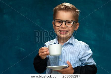 Portrait of stylish business child wearing eyeglasses having break with cup of drink. Cute caucasian boy imitating businessperson or office worker.