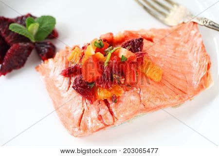 Portion of salmon with a salsa made of tomatoes scallions and blood oranges