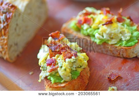 Toasted whole grain bread with avocado scrambled eggs and bacon