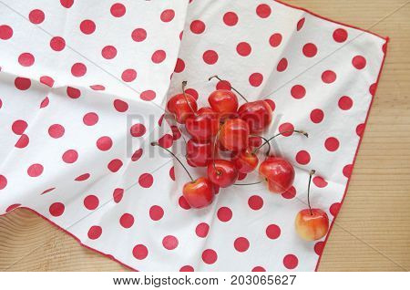 Fresh cherries on a white napkin with red polka dots