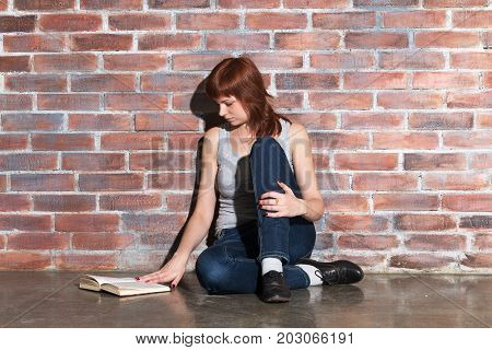 Beautiful young red hair woman in jeans with book sitting on floor near brick wall. Attentively reading an interesting book