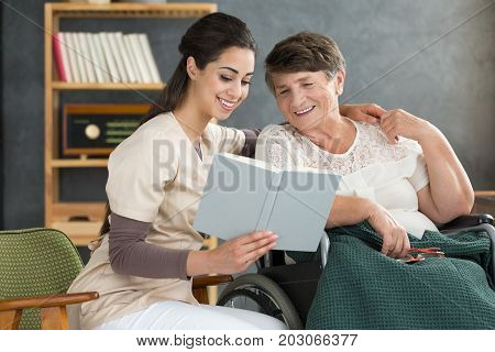 Nurse And Woman Reading Together
