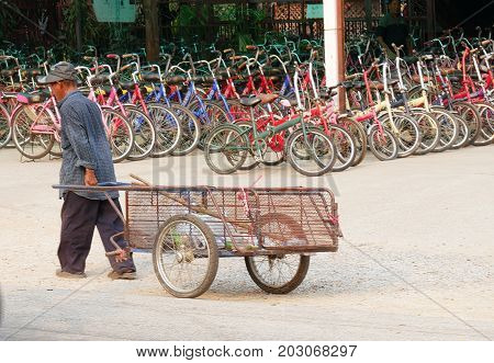 OLD SUKHOTHAI CITY, THAILAND--A man pulls an empty cart with wheels near a shop with bikes for rent at the Old Sukhothai City in March 2016.