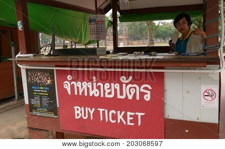 OLD SUKHOTHAI CITY, THAILAND--A woman manning a small open bus ticket stall at the Old Sukhothai City in the northern part of Thailand in March 2016.