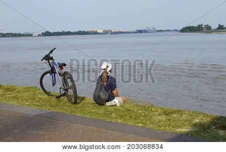 NEW ORLEANS, LOUISIANA--A woman stops for rest with her bicycle beside the Riverwalk along the banks of Mississippi River in August 2015.