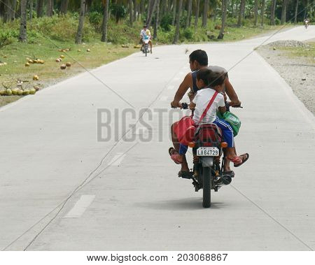 DAVAO ORIENTAL, PHILIPPINES--Two children ride in tandem behind an adult driving a motorcycle along the main highway in Davao Oriental in March 2016.