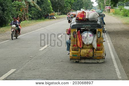 DAVAO  DEL NORTE, PHILIPPINES--A motorcycle with yellow sidecar, called a tricycle or pedicab overloaded with various cargo at the national highway in Mabini, Davao del Norte, southern Philippines in March 2016.