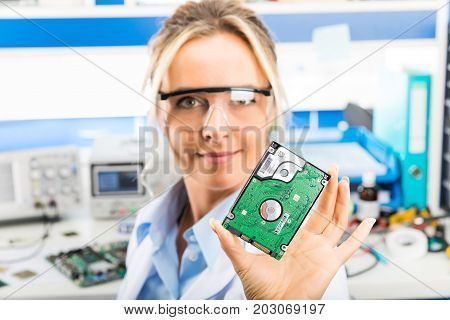 Young attractive happy smiling female digital computer electronic engineer with protective sunglasses holding 2.5 inch laptop or notebook HDD hard disk drive in hand in the laboratory