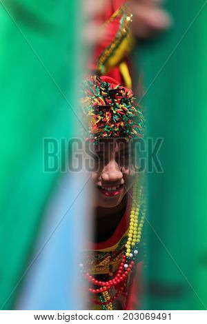 DAVAO CITY, PHILIPPINES--AUGUST 2014: A girl peeks out through bamboo poles at the parade grounds. Kadayawan is celebrated August each year to give thanks for life and an abundant harvest.