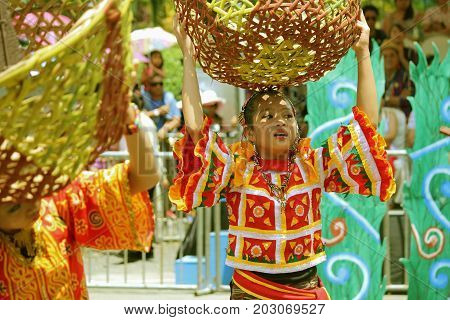 DAVAO CITY, PHILIPPINES--AUGUST 2014: Girls carrying big empty baskets as props at the streetdancing parade. Kadayawan is celebrated August each year to give thanks for life and an abundant harvest.