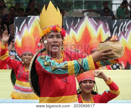 DAVAO CITY, PHILIPPINES--AUGUST 2014: Street dancers perform with fire ritual at the parade. Kadayawan is celebrated August each year to give thanks for life and an abundant harvest.
