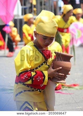 DAVAO CITY, PHILIPPINES--AUGUST 2014: A girl joins the streetdancing competition with an earthen jar at the parade. Kadayawan is celebrated August each year to give thanks for an abundant harvest.