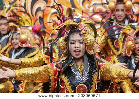 DAVAO CITY, PHILIPPINES--AUGUST 2014: Streetdancers in colorful costumes at the parade for the Kadayawan. Kadayawan is celebrated August each year to give thanks for life and an abundant harvest.