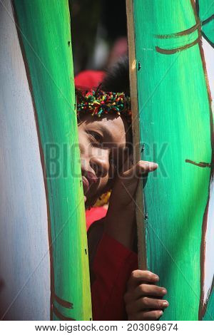 DAVAO CITY, PHILIPPINES--AUGUST 2014: A participant peeks out thorugh bamboo poles at the parade grounds. Kadayawan is celebrated August each year to give thanks for life and an abundant harvest.