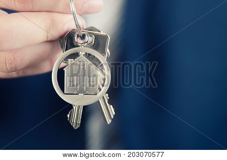 Real Estate Agent Holding Key Of New Apartment Close Up