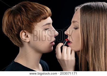 Woman Applying Lipstick Onto Girlfriend
