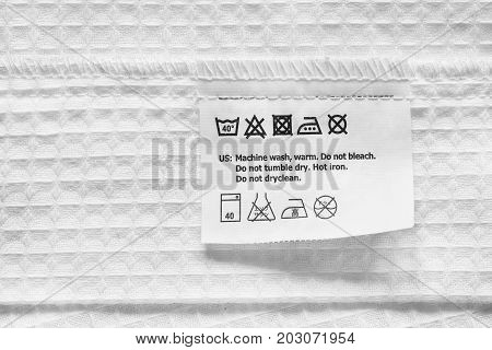 Washing instructions clothes label on white cotton as a background
