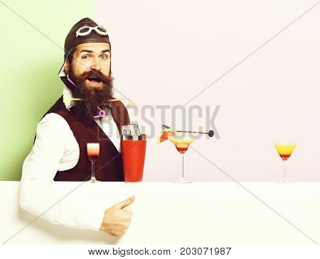 handsome bearded aviator or pilot with beard and mustache on smiling face with shaker alcoholic cocktails in vintage suede leather waistcoat with hand and glasses on purple green studio background