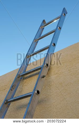 Aluminum ladder rising toward the sky over a flat roofed adobe building
