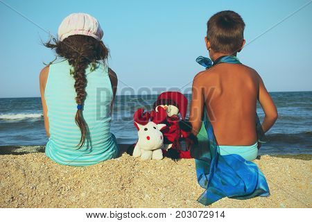 Christmas, people, children concept. Kids sitting on the beach with Christmas toys. back view.