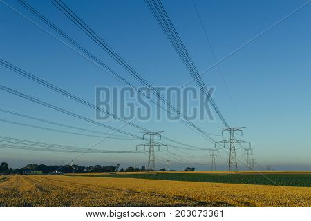 High Voltage Power Lines And Transmission Towers In Agricultural Fields In Normandy, France. Electri