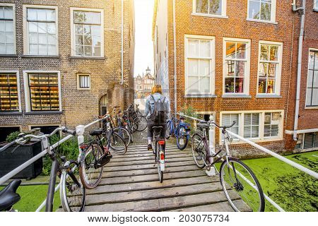 Woman riding a bicycle on the bridge in Delft town during the morning light, Netherlands