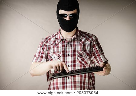 Crazy hacker man. Unrecognizable guy wearing black balaclava holding computer keyboard. Hate speech on the internet.