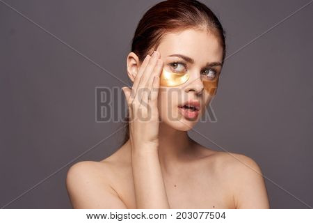 woman in gold patches for eyes, facial treatment, portrait.