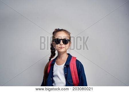 little girl in sunglasses on a gray background.