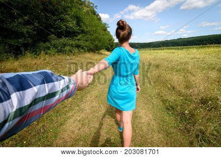 Follow me in nature. Beautiful young brunette woman in blue dress holding man hand with cloudy blue sky background free space. Couple walking hand in hand in field. Travel and journey concept