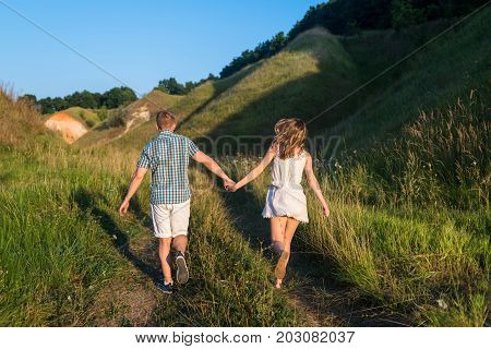 Young Loving Couple Walking On Green Field Near Hills, Free Space. Young Beautiful Couple Of Travele