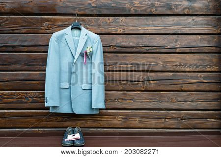 Stylish elegant wedding groom suit with buttonhole hanging on wooden background with copy space. Gray suit hangs above leather groom shoes and pink bowtie. Groom wedding accessories free space