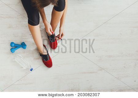 Fitness background, copy space. Woman tying up lace on sport shoes top view, preparing for training, wearing sneakers.