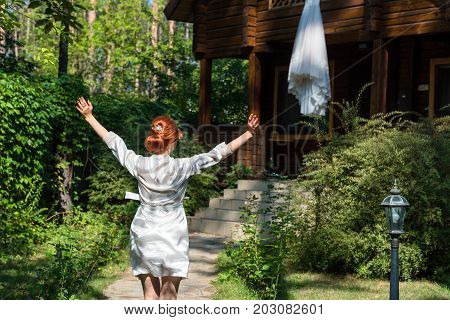 Beautiful redhead bride in silk dressing gown running with hands up to her wedding dress hanging on wooden house in the forest free space. Wedding morning preparation in sunny summer day