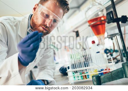 Attractive male student of chemistry working in laboratory