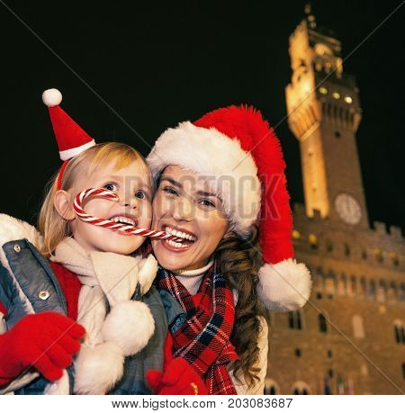 Mother And Child Eating Christmas Candy Cane In Florence, Italy
