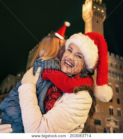 Mother And Daughter In Christmas Hats In Florence Embracing