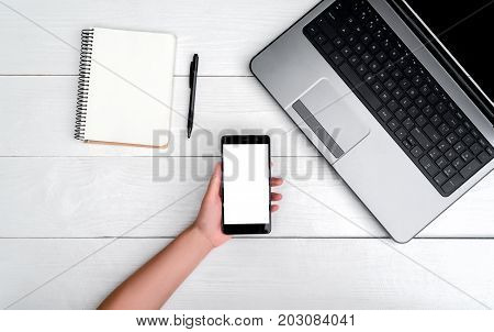 Top View On White Wooden Table With Open Laptop Computer, Cell Phone In Girl's Hand And Blank Empty