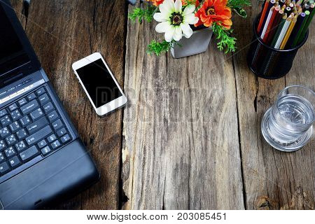 Top View Of Laptop ,white Phone Pencils Case , A Glass Of Water On Wood Table With Flowers In  Vase