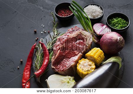 Raw rib eye steak with herbs and vegetables. Cooking ingredients for restaurant dish. Fresh meat, spices, eggplant, onion, pepper, corn on plate on black background
