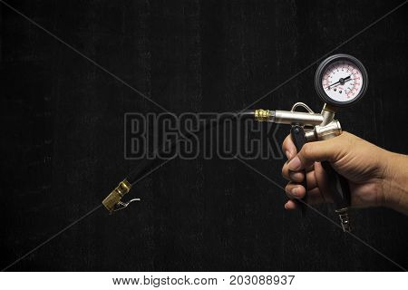Hand holding an inflator gauge tools Hand of mechanic man checking air pressure gauge of car tyre with black painted cement wall background with copy space for writing text Automotive parts concept.